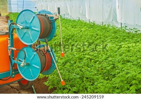 the irrigation tool in modern greenhouse close up rear view horizontal version - stock photo