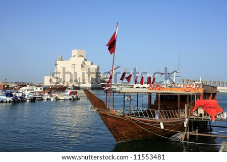 The Islamic art museum in Doha, Qatar, seen from across the Dhow harbour in Doha Bay, with a boat dressed overall in Qatari flags in the foreground. - stock photo