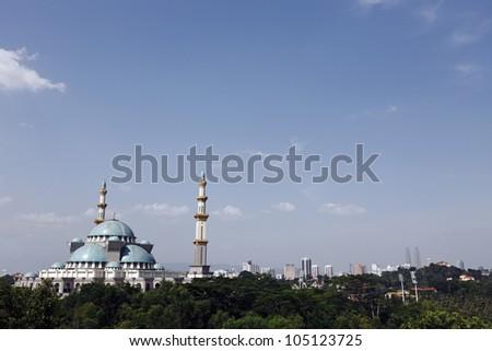 The Islamic Federal Territory Mosque in the city skyline of Kuala Lumpur, Malaysia. - stock photo
