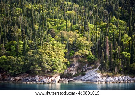 The Island of Kefalonia, Ionian Sea, Greece. A view of Mediterranean cypress trees fringing the azure waters of the Ionian Sea on the east coast of the Greek island of Kefalonia. - stock photo