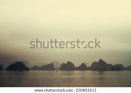 The islands of Halong Bay, a UNESCO World Heritage Site, emerge from an ethereal sea mist. This image has been treated to give it a vintage effect, enhancing the ambiance and mystique. - stock photo