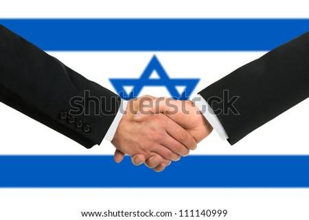 The Israeli flag and business handshake - stock photo