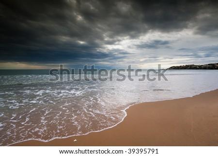 The italian beach of Serapo in Gaeta under a stormy and cloudy sky and wavy sea - stock photo