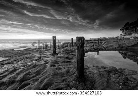 The Ivo Rowe natural rockpool with textured weathered and eroded rocks and timber and chain fence - stock photo
