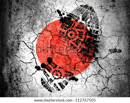 The Japan flag painted on  cracked ground with vignette with dirty oil footprint over it - stock photo