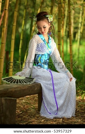The Japanese with a fan, sitting on a bench in bamboo wood