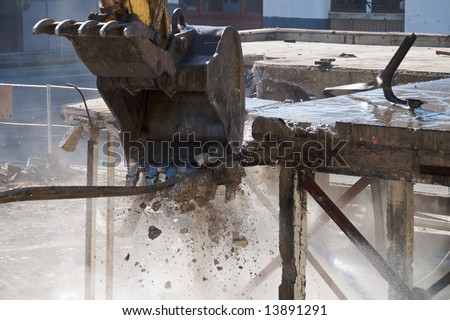 The jawed bucket of a mechanical excavator breaking a concrete floor in a demolition site - stock photo