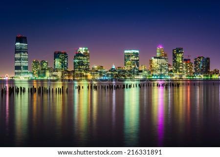 The Jersey City Skyline at night, seen from Pier 34, Manhattan, New York. - stock photo