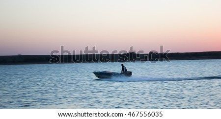 the jet ski above the water at sunset