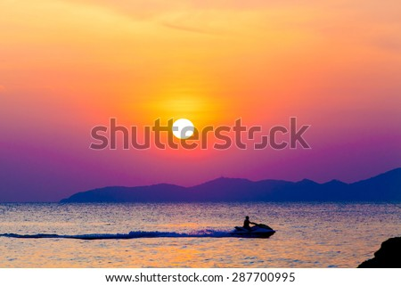 the jetski above the water at sunset.  Silhouette of people on a jet ski running pass the romantic sunset in the sea. - stock photo