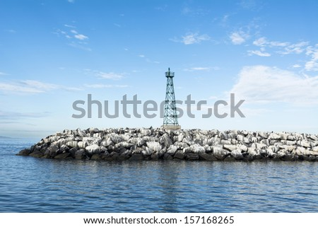 The jetty breakwater at the entrance of Ensenada harbor in Mexico. - stock photo