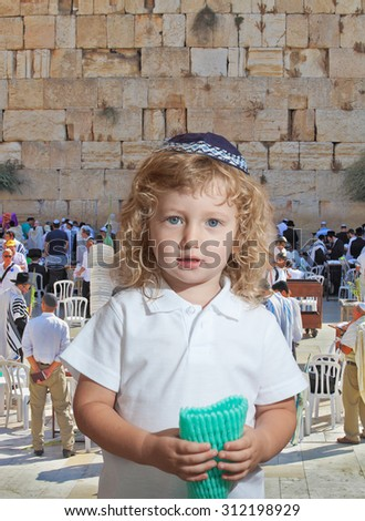 The Jewish holiday of Sukkot. Adorable little boy with long blond curls and blue eyes in  knitted skullcap. He stands at main Jewish shrine - the Western Wall of Temple - stock photo