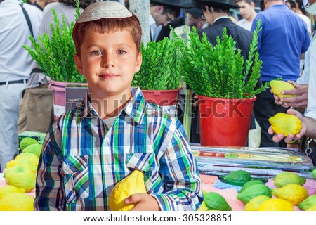 The Jewish holiday of Sukkot. Seven year old boy in white skullcap with etrog. He stand  on a pre-holiday market in Jerusalem. Ritual plants - myrtle prepared for sale  - stock photo