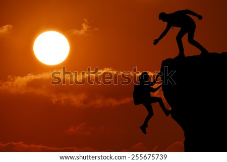 The joint work teamwork of two people man and girl travelers help each other on top of a mountain climbing team, a beautiful sunset landscape with big sun - stock photo
