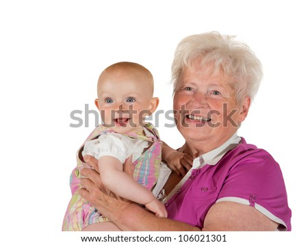 The joy of being a grandmother, a beaming, joyful young baby and doting grandmother smile happily for the camera while posing for a studio portrait - stock photo