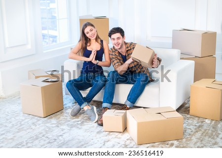 The joy of moving into the house. A loving couple holding box in hands and looking at the camera while a young and beautiful couple in love sitting on the couch in an empty apartment among boxes