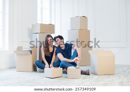 The joy of moving into the house. A loving couple holding box in hands and looking at the camera while a young and beautiful couple in love sitting on the floor in an empty apartment among boxes - stock photo