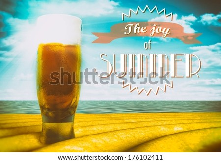 The joy of summer sign with beer glass on beach - stock photo
