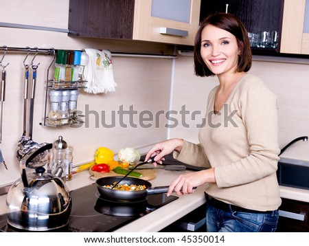 The joyful beautiful woman is on the kitchen prepares to eat - stock photo