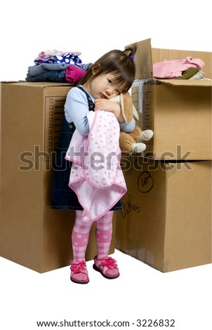 The joys of moving from one place to another. A young girl hugs her bunny as her bedroom is packed up - stock photo