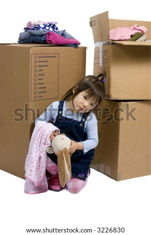 The joys of moving from one place to another. A young girl looks sad as her bedroom is packed up for a move - stock photo