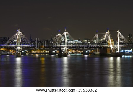 The Jubilee Bridge in London at night with reflection in the river Thames - stock photo