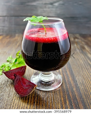 The juice of beet in wineglass, beet slices and parsley on a wooden board background - stock photo