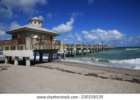 The Juno Beach Fishing Pier on the Atlantic Ocean. - stock photo