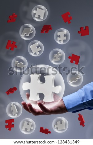 The key piece of a solution concept - puzzle pieces in glass bubbles - stock photo