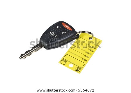 The key to your new car!  Bright yellow dealership key tag is blank.  Key has push buttons for trunk release, lock, unlock, and panic.  Isolated on white. - stock photo