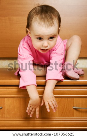 The kid can not come down from a height. - stock photo