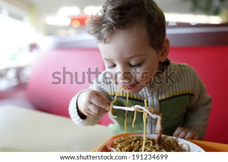 The kid eating spaghetti in the restaurant - stock photo