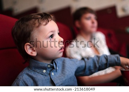 The kid has popcorn in the cinema - stock photo