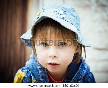 The kid looked into carefully before against the wall. - stock photo