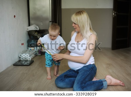 the kid measures the size of a stomach of the pregnant mother - stock photo