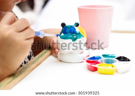 The kid painting color on the plaster statue - stock photo