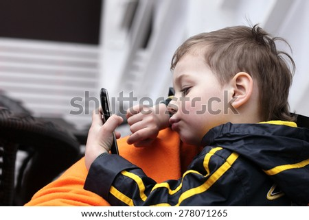 The kid playing with smartphone in the cafe - stock photo