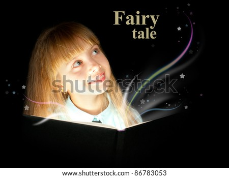The kid reading a book of fairy tales and dreaming - stock photo
