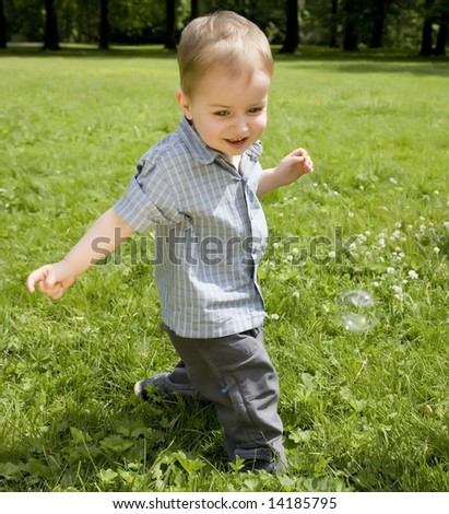 The Kid Running On A Green Meadow - stock photo