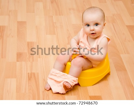 The kid was sitting on the pot. - stock photo