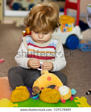 The kid with toys at home. Portrait of a boy at home