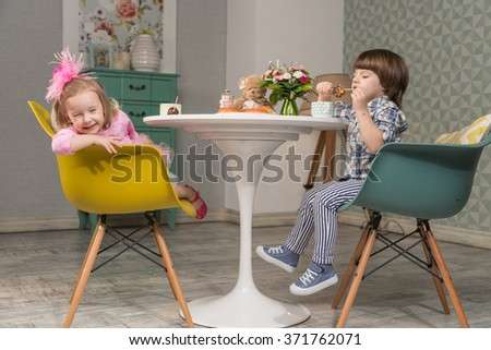 The kids eat breakfast at the table. Girl laughing. Couple Concept - stock photo