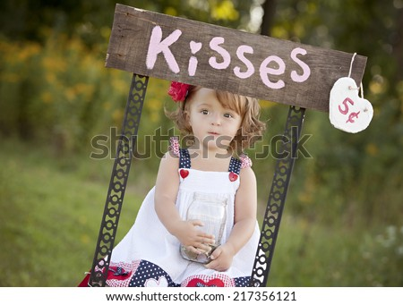 The Kissing Booth.  Adorable little girl sitting at a kissing booth. - stock photo