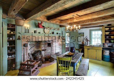 The kitchen, dining room and fireplace in a 17th century primitive colonial style home.  This home dates to before the American revolutionary war, and contains antiques from the late 18th century. - stock photo
