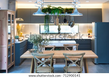 The kitchen is decorated in a cool white mini-tone with a wooden table, wooden chairs for dining. Decorated with lamps and kitchen accessories.