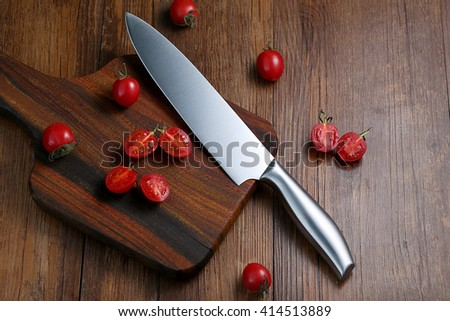 The kitchen knife and cut the tomatoes on the board - stock photo
