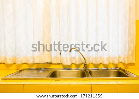 The kitchen sink and a yellow tiles - stock photo