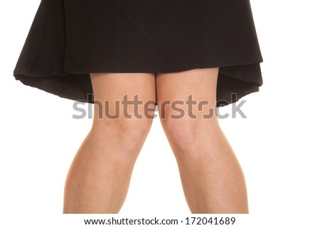 The knees of a woman in a black skirt. - stock photo
