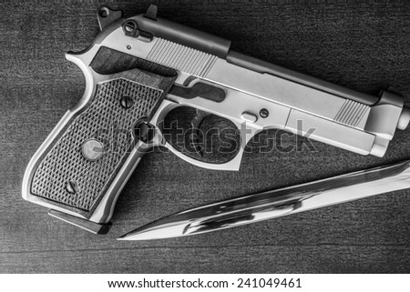 The knife and the pistol on the table. Top view - stock photo