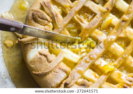 The knife cuts the orange pie, tart with jam and lemon - stock photo